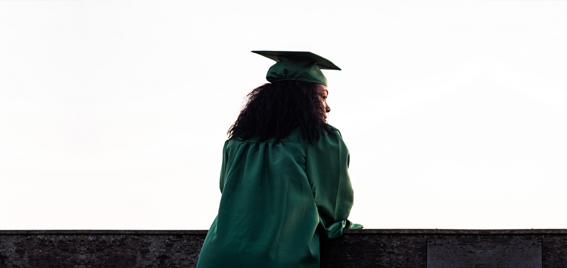 A black woman in a graduation cap and gown looking over a balcony