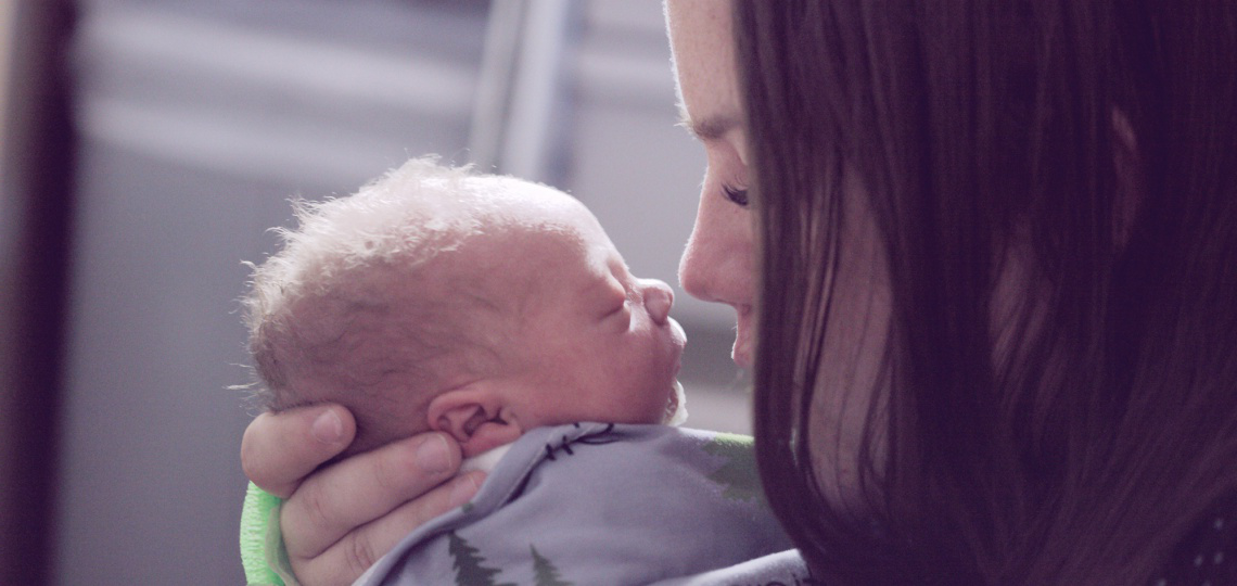 a mother holding her baby close to her face so that their noses almost touch