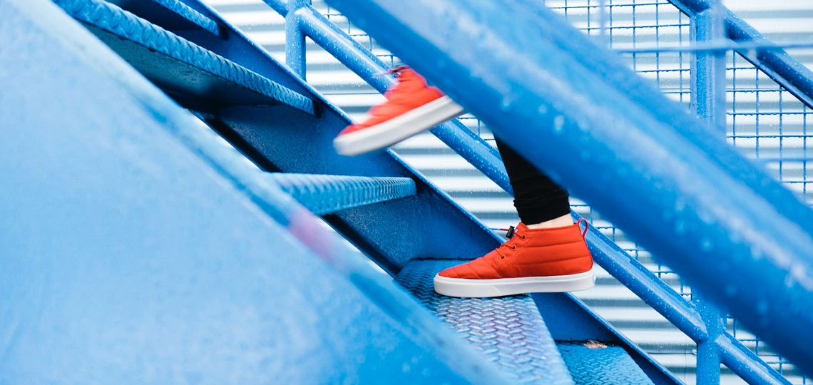 A person in red high top sneakers stepping up wet, blue stairs