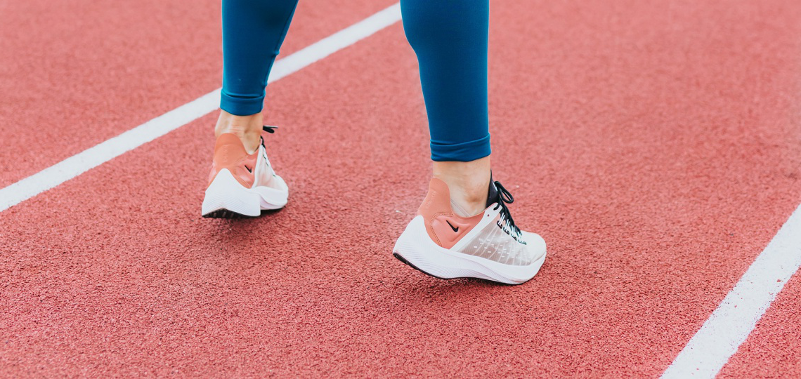 A runner in blue leggings and grey and pink shoes, standing on their toes on an outdoor track between two white lines