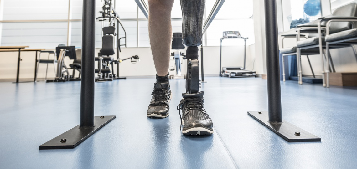 Person standing in a lab with a prosthetic leg on