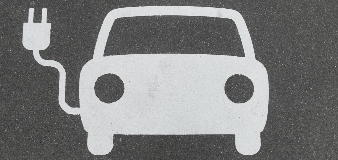 A painted icon of a car with an electric plug attached to it, on pavement