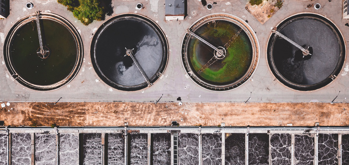 aerial view of four tanks of water at a wastewater treatment facility