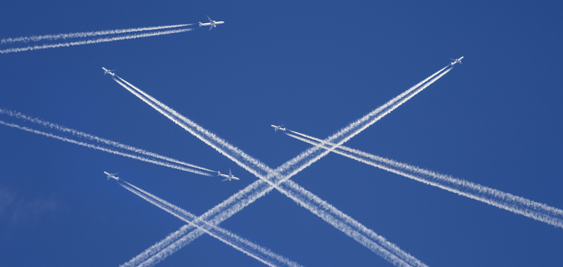A photo collage of six airplanes flying in a clear blue sky and leaving white exhaust trails behind them
