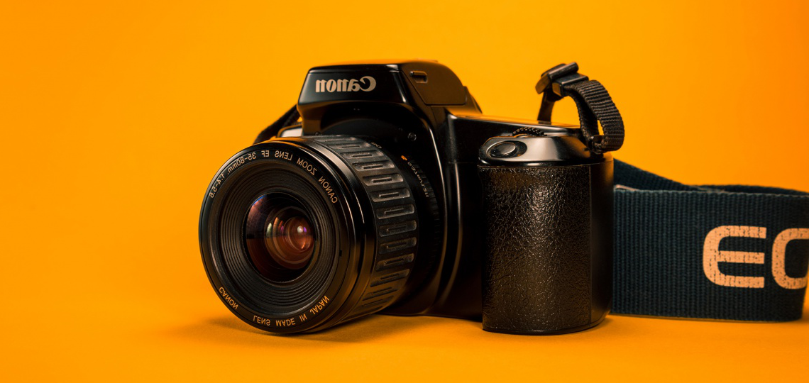 a Canon camera on an orange background